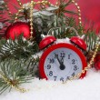 Green Christmas tree with toy and clock in the snow on red — Stock Photo #13208970