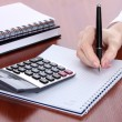 Women hands with pencil, notebooks and Calculator on wooden table - Stock Photo