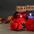 Memory lantern with candles, red carnations and St. George ribbon on wooden - Stock Photo