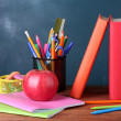 Composition of books, stationery and an apple on the teacher's desk in the — Stock Photo