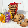 Chocolate chips cookies with red ribbon and wildflowers on wooden table — Stock Photo #13209115