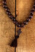 El rosario de madera en primer plano de fondo de madera — Foto de Stock