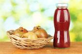 Bottle of pomegranate juice and pomegranates on green background close-up — Stock Photo