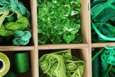 Green thread and material for handicrafts in box close-up — Stock Photo