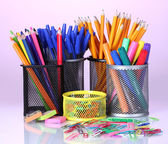 Color holders for office supplies with them on bright background — Stock Photo