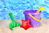 Children's beach toys on sand on water background — Stock fotografie