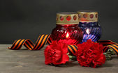 Memory lantern with candles, red carnations and St. George ribbon on wooden — Stock Photo