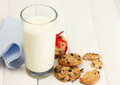 Glass of milk and chocolate chips cookies with red ribbon on wooden table — Stock Photo