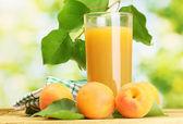 Szkło sok z moreli i świeże morele na drewnianym stole na zielony backgrou — Zdjęcie stockowe