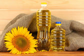 Sunflower oil and sunflower on wood background — Stok fotoğraf