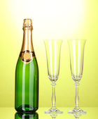 Bottle of champagne and goblets on green background — Stock Photo
