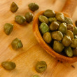 Stock Photo: Green capers in wooden spoon on wooden background close-up