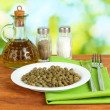 Capers in the plate on bright green background — Stock Photo