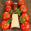 Ketchup in bottle and tomatoes on wooden table — Stock Photo #13210328