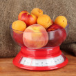 Ripe fruit in kitchen scales on canvas background close-up -  