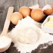 Eggs, flour and butter close-up on wooden table — Stock Photo #13210957