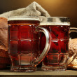 Tankards of kvass and rye breads with ears, on wooden table on brown backgr — Stock Photo