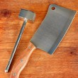 Meat hammer with meat hatchet on wooden background close-up — Stock Photo