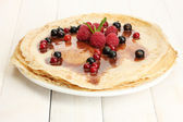 Delicious pancakes with berries and chocolate on plate on wooden table — Stock Photo