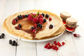 Delicious pancakes with berries and jam on plate on wooden table — Stock Photo