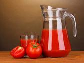 Sok pomidorowy w dzban i szkło na drewnianym stole na brązowym tle — Zdjęcie stockowe