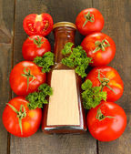 Ketchup in bottle and tomatoes on wooden table — Stock Photo