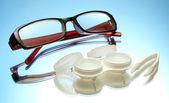Anteojos, lentes de contacto en contenedores y pinzas sobre fondo azul — Foto de Stock
