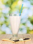 Vanille melk shake op houten tafel op lichte achtergrond — Stockfoto