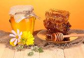 Pot de miel et nid d'abeille sur une table en bois sur fond orange — Photo
