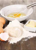 Eggs, flour and butter close-up on wooden table — Stock Photo