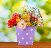 Purple bucket with white polka-dot with flowers on green background — Stock Photo