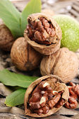 Walnuts with green leaves, on wicker background — Stock Photo