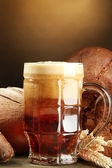 Tankard of kvass and rye breads with ears, on wooden table on brown backgro — Stock Photo
