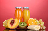 Delicious multifruit juice in a bottle and fruit next to it on pink backgro — Stock Photo