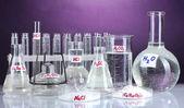 Tubos de ensayo con varios ácidos y productos químicos sobre fondo brillante — Foto de Stock