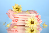 Panty liners in individual packing and yellow flowers on blue background cl — Stock Photo