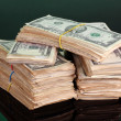 Stacks of dollars on green background — Stock Photo