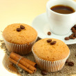 Tasty muffin cakes with spices on burlap and cup of coffee, on beige background — Stock Photo