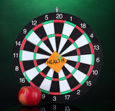 Darts with a sticker symbolizing health on colorful background — Stock Photo