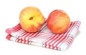 Rijpe perziken op servet geïsoleerd op wit — Stockfoto