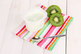 Yogurt with kiwi on napkin on wooden background — Foto de Stock