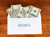 The envelope with the money bills on wooden background. Bribes. — Stock Photo