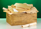 Wooden crate with papers and letters on green background — Stock Photo