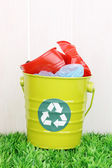 Recycling bin on green grass near wooden fence — Stock Photo