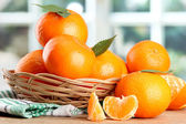 Tangerines with leaves in a beautiful basket, on wooden table on window background — Stok fotoğraf
