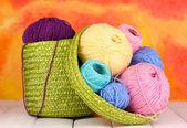 Bunte garne für strickmaschinen in grünen korb auf weißer holztisch auf colorfu — Stockfoto