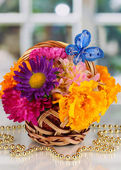 Hermoso ramo de flores en la canasta pequeña con nota de papel sobre la mesa blanca sobre fondo de ventana — Foto de Stock