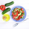 Fresh salad with tomatoes and cucumbers on white wooden background — Stock Photo