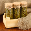 Glass jars with tinned capers on sack background close-up — Stock Photo