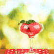 Watermelon ice cream in a glass on green background close-up - Stock Photo